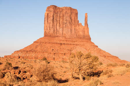 Sunset and strong colors at the buttes in The Monument Valley, Navajo Indian tribal reservation park. Deep blue sky with cloudy and red sand dust in a rough plateau Stok Fotoğraf