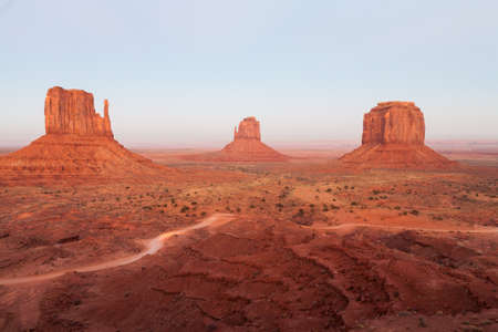 Sunset and pale colors at the West and East Mittens and Merrick buttes in The Monument Valley, Navajo Indian tribal reservation park. Deep blue sky with cloudy and red sand dust in a rough plateau