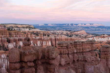Great spires, also called hoodos, carved away by erosion in Bryce Canyon National Park, Utah, USA, shine red, orange and pastel during sunset.