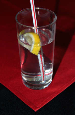 cocktail of gin and tonic and a lemon on the table with a red cloth Stock Photo