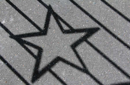 black pentagonal starlike shadow on the pavement