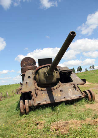 an old Soviet tank lined under the peaceful blue sky