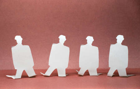 Paper images of people standing on their knees Stock Photo