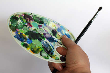 palette and brush in hand of the artist Stock Photo