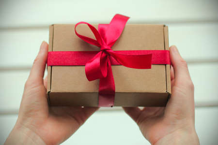 a gift in a package with a ribbon in the hands Stock Photo
