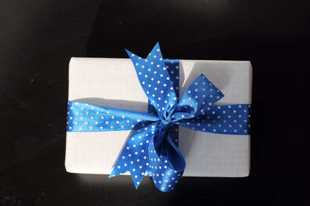 festively: festively packaged in a gift paper and tied with a blue ribbon