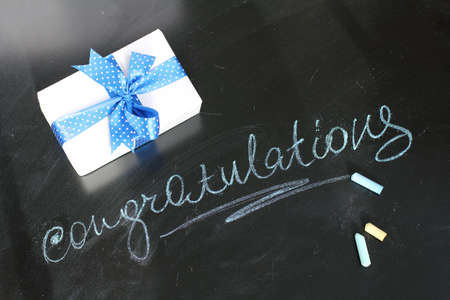 blue steel: a gift and a congratulation on a holiday written on a blackboard with chalk