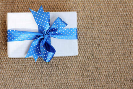 a gift with a blue ribbon with polka dots