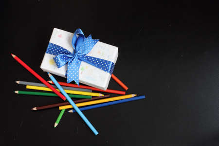 festively: a set of pencils and festively wrapped gift with childrens drawings Stock Photo
