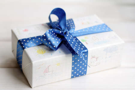 festively: festively wrapped gift with childrens drawings in pencil