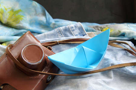 paper boat: nostalgic background with old camera and blue paper boat