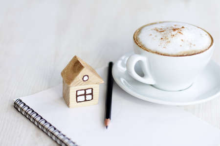 housing lot: Cappuccino with milk foam and layout of the house with a notebook open for entries
