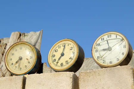 the past: broken old clock show different past time