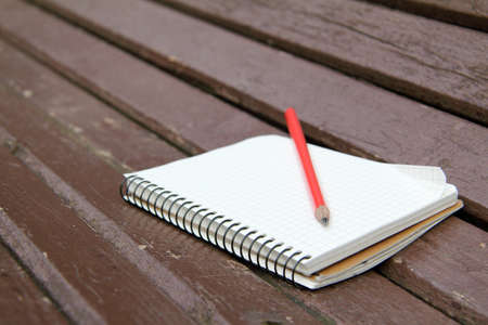 sketchbook: sketchbook and a pencil lying on a wooden bench