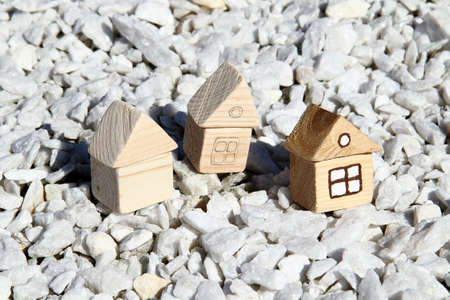 Three wooden toy house standing in a light stone
