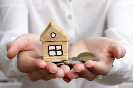 housing lot: man holds in hands money with a home
