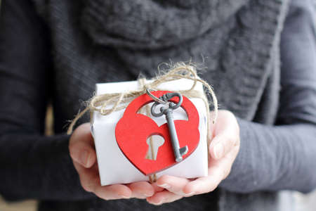 warm background with a gift and attached to it the key and heart Stock Photo