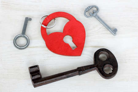 the symbolic heart of the padlock and a lot of different keys next Stock Photo