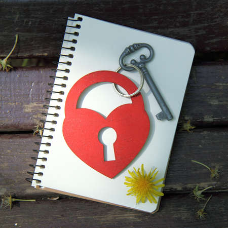 dedicate: lock key symbol and heart on a notebook with a pencil top view  unusual love letter