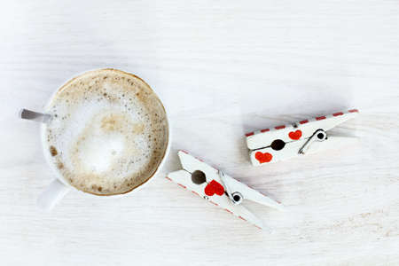 frothy cappuccino placed on a table on which is a pair of lovers clothespins  craving love and coffee Stock Photo
