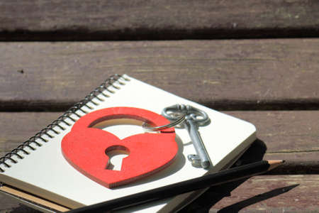 love notes: heart symbol in the form of a padlock with key on a background of a notebook with a pencil on a wooden background  love notes Stock Photo