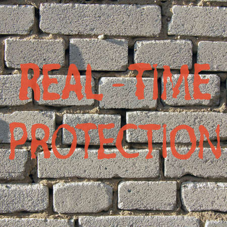 red inscription real-time protection against a background of white brick wall  real-time protection Stock Photo