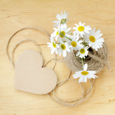 bouquet of daisies on a wooden table and a simple heart symbol top view  retro romantic story Stock Photo