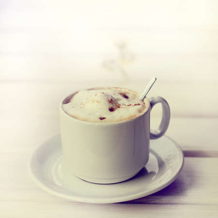 frothy cappuccino with cinnamon in a white mug and spoon  retro coffee Stock Photo
