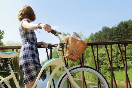 woman stopped to rest on the bridge while walking on a bicycle  bicycle is an excellent time for a walk summer Stock Photo