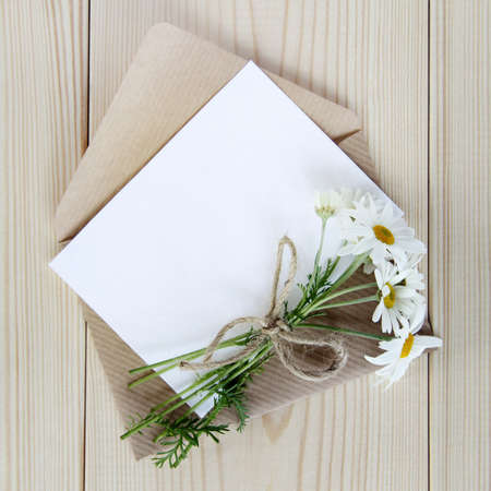 bouquet of wild daisies with an envelope and a card to wish a top view  festive flower letter