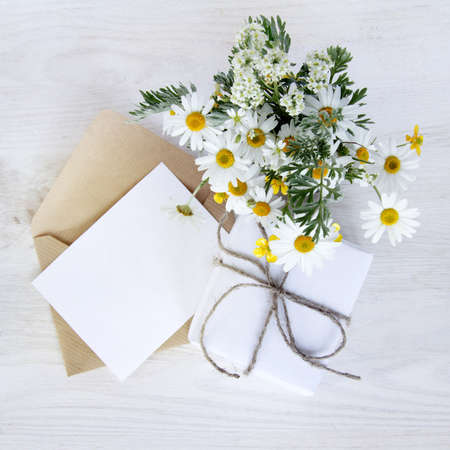 bouquet of wild flowers with a gift and an envelope with a card to wish a top view  holiday gift set