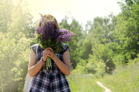 girl in a plaid summer dress hiding her face behind a bouquet of wild flowers  floral hide and seek outdoors