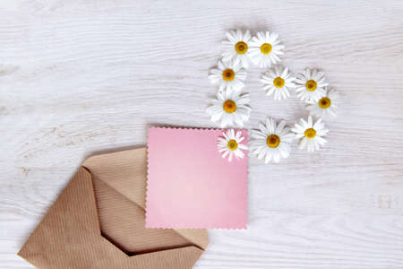 flat lay, with pink flowers daisies postcard for clean inscriptions peeping out of the envelope, top view  letter with the symbol of flowers heart Stock Photo
