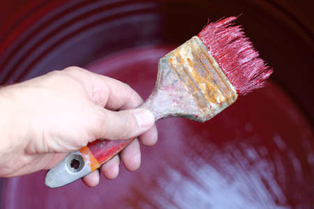 Painter is working on paint brush barrels of water with red paint  painting of work is finished Stock Photo
