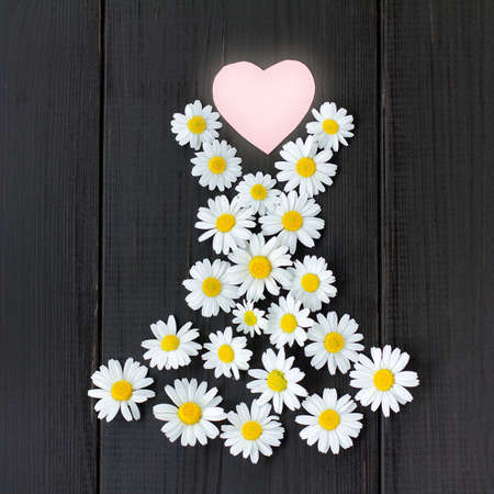 flat lay of your favorite summer dress daisies with heart symbol on wooden background  fashionable floral dress from your favorite collection Stock Photo