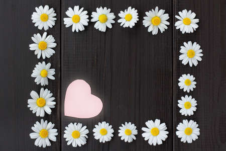 flat lay of daisies forming a frame on a dark wooden background with heart symbol in top view  romantic floral frame Stock Photo