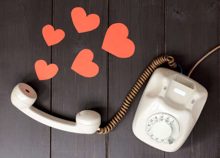 idea attractive voice in the form of hearts flying out of telephone handset lying on a wooden table  amorous talking by phone