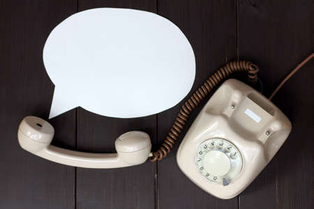retro phone and the concept of the voice coming out of the tube lying on a wooden table top view  important telephone conversation Stock Photo
