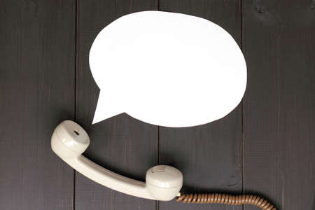 handset lying on a wooden table and departing from it idea talking  sound from telephone handset Stock Photo