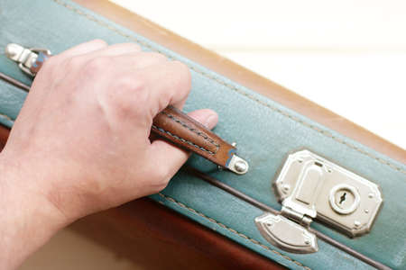 human hand holds the handle of the suitcase retro top view  travel with a suitcase in hand