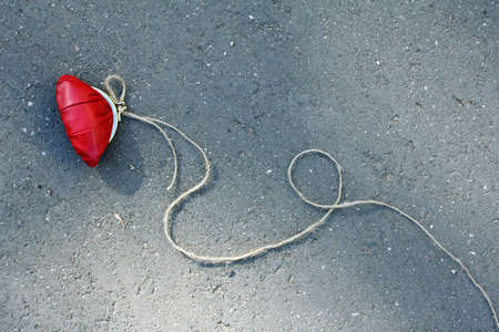 red purse with a rope tied to it is on the road view from above  caution dangerous bait