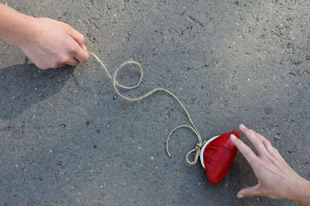 man with a red purse and tied a rope to it entices another person  danger of easy money Stock Photo
