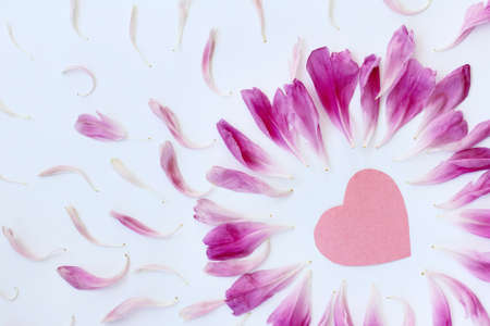 flat lay with a paper heart is surrounded pink petals top view  heart with delicate petals background Stock Photo