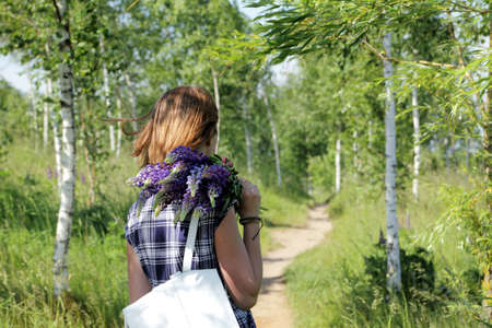 girl in a summer dress walking with a bouquet flowers on the forest path  outdoor recreation