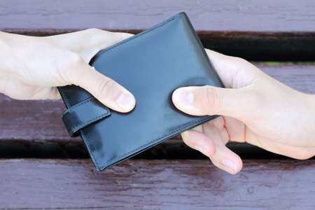 black purse dragging in different directions two human hands  struggle for the purse Stock Photo