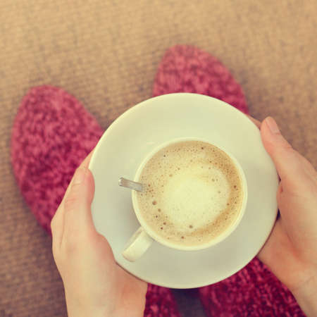 warm home: frothy coffee with milk in the hands of the person clothed in warm socks, top view  coffee in a warm home environment