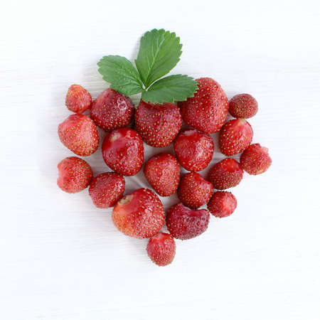 lot of ripe red berries on a light wooden background in the form of large strawberries with flower and leaves top view  strawberries from strawberry