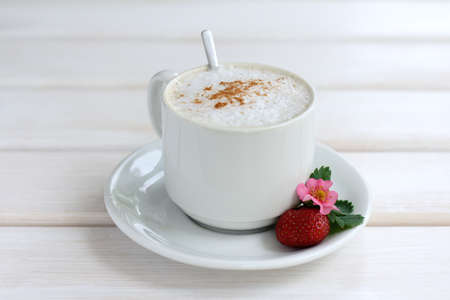 frothy coffee with cinnamon and with decoration of berry, flower and leaf strawberries  coffee with the aroma of cinnamon and strawberry Stock Photo