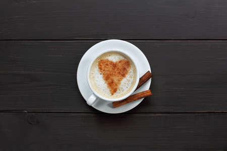 lactic: drawing a heart casting up cinnamon in a cup of cappuccino on dark wooden background top view  magic cinnamon sticks for a coffee