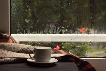 hot cup, frothy coffee in the warm cozy home atmosphere / when behind a window passed a rain Foto de archivo